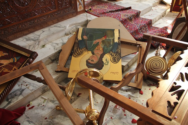 Icons and overturned furniture on the ground at the church of Saint Michael in the Syrian village of Qara