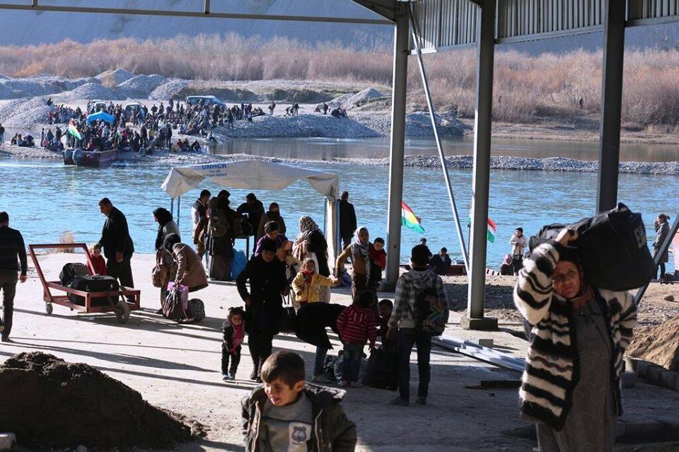 Syrian refugees cross the Tigris river to seek refuge in Iraq